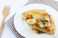 Scheibe der geschmackvollen Pizza auf der Platte Stockfotos