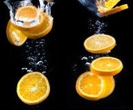 Scheibe der Orange im Wasser mit Blasen Lizenzfreie Stockfotos
