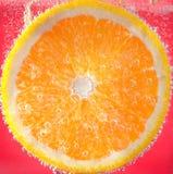 Scheibe der Orange im Wasser mit Blasen, auf rotem Hintergrund Stockbilder
