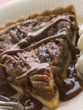 Scheibe der Pekannuss-Torte mit Karamell-Soße und einer Gabel Stockfotos