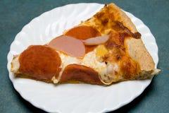 Scheibe der Pizza überstieg mit Pepperonis und Speck. Stockfotos