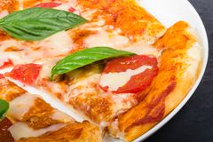 Scheibe der Pizza mit Basilikumblatt stockfoto