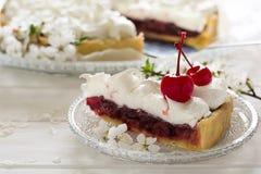 Scheibe der selbst gemachten Torte mit Kirsche und Meringe Stockfotografie