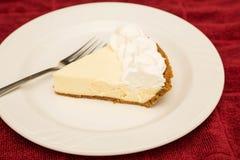 Scheibe der Torte der echten Limette auf weißer Platte und rotem Tuch Stockfotos