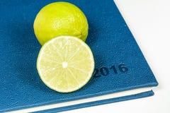 Scheibe der Zitrone auf blauem Tagebuch Stockbilder
