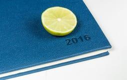 Scheibe der Zitrone auf blauem Tagebuch Lizenzfreies Stockfoto