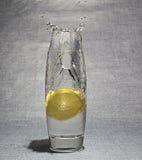 Scheibe der Zitrone fiel in Glas Wasser Stockbilder