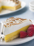 Scheibe der Zitrone-Meringe-Torte mit Himbeeren Stockbild