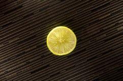 Scheibe der Zitrone oder des Kalkes auf schwarzem Hintergrund mit Streifen Lizenzfreie Stockfotos