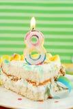 Scheibe des achten Geburtstagkuchens Stockbild