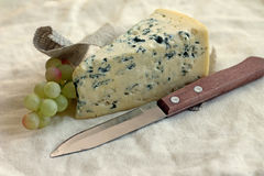 Scheibe des Blauschimmelkäses mit Messer und Trauben Stockfotografie