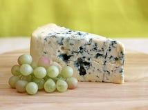 Scheibe des Blauschimmelkäses mit Trauben auf grünem Hintergrund Stockfotografie