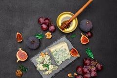 Scheibe des französischen Roquefortkäses und -früchte auf Steinbrett Lizenzfreie Stockfotografie