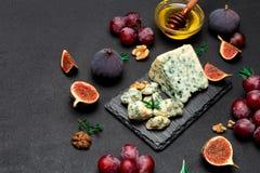 Scheibe des französischen Roquefortkäses und -früchte auf Steinbrett Lizenzfreies Stockbild