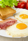 Scheibe des gebratenen Speckes, zwei Eier auf der Platte mit Toast zum Frühstück Lizenzfreie Stockfotos