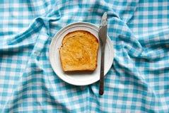 Scheibe des gebutterten Toasts auf einer Platte Lizenzfreie Stockbilder