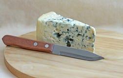 Scheibe des geschmackvollen Blauschimmelkäses mit Messer Stockbild