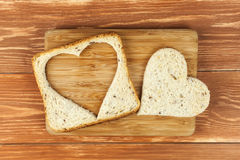 Scheibe des Getreidetoastbrotes mit herausgeschnittenem Herzen Stockbild