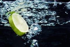 Scheibe des Kalkes (Zitrone) fallend in Wasser Lizenzfreie Stockbilder