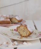 Scheibe des Kuchens Ciambellone mit Krumen auf der keramischen Platte gemalt mit Blumenmotiven, Stofftuch und Perlmuttfragmenten Lizenzfreies Stockfoto