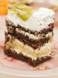 Scheibe des Kuchens mit Schokolade, Schlagsahne und Frucht Lizenzfreie Stockfotos