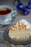 Scheibe des Meringekuchens und der Tasse Tee und Iris lizenzfreie stockbilder