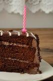 Scheibe des Schokoladenkuchens mit einer rosa Geburtstagskerze Stockfotos