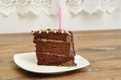 Scheibe des Schokoladenkuchens mit einer rosa Geburtstagskerze Stockbild