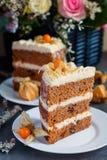 Scheibe des selbst gemachten Karottenkuchens mit einem Korb von frischen Blumen auf dem Hintergrund Lizenzfreies Stockbild