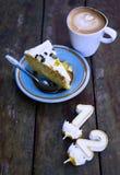 Scheibe von Geburtstagskuchen witn Kerze nummeriert ein und zwei mit Schale Latte auf Holztisch im warmen Sonnenlicht stockbild