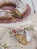 Scheibe von Kuchen ` Ciambellone-` mit Krumen auf der keramischen Platte gemalt mit Blumenmotiven Lizenzfreies Stockfoto