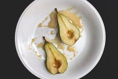 Scheibe zwei der grünen Birne mit Honigsirup auf Draufsicht der weißen Platte Lizenzfreies Stockfoto