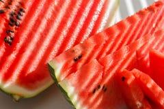 Scheiben bessert rote Wassermelone, Sonnenlichtstreifen auf blauer Platte aus Stockfotos