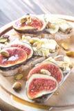 Scheiben brot mit Camembert, Feigen und Pistazien Lizenzfreie Stockfotografie