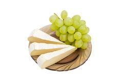 Scheiben der Brie und der Trauben auf Untertasse Lizenzfreie Stockfotografie
