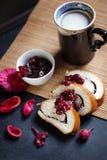 Scheiben der Buttermohnblume rollen, gedient mit Kirschmarmelade und großer keramischer Schale mit heißem Getränk Stockfoto