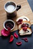 Scheiben der Buttermohnblume rollen, gedient mit Kirschmarmelade und großer keramischer Schale mit heißem Getränk Lizenzfreies Stockfoto