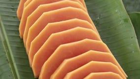 Scheiben der frischen rohen exotischen tropischen thailändischen Frucht Carica Papaya drehend auf Bananen-Blatt stock video footage