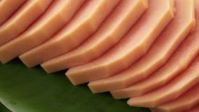 Scheiben der frischen rohen exotischen tropischen thailändischen Frucht Carica Papaya drehend auf Bananen-Blatt stock video