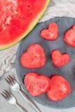 Scheiben der frischen samenlosen Wassermelone schnitten in Herzform auf Schieferbrett, die Ebenenlage, vertikal lizenzfreies stockfoto