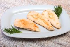 Scheiben der gebratenen Hühnerbrust und der Tomate auf weißer Platte Stockfotos