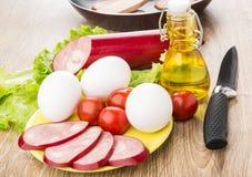 Scheiben der geräucherten Wurst, Tomaten, Eier in der Platte, Pflanzenöl Stockfotografie