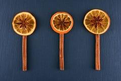 Scheiben der getrockneten Orange mit Sternanis und Zimtgewürz auf dunklem Hintergrund Gewürze werden in Form von Blumen gezeichne Stockbild