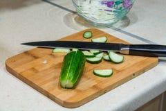 Scheiben der Gurke und des Messers auf dem Schneidebrett Lizenzfreies Stockfoto