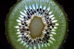 Scheiben der Kiwi auf Kiwihintergrund Stockfotografie