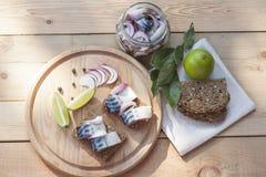 Scheiben der marinierten Makrele mit Zwiebel in einem Glas, in einem Kalk, in einem Lorbeer und in einem Brot auf hölzernem Brett Stockbilder