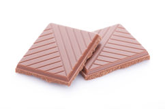 Scheiben der Milchschokolade auf weißem Hintergrund Stockbilder