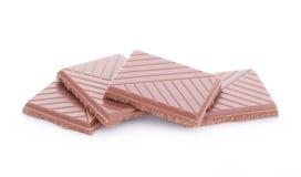 Scheiben der Milchschokolade auf weißem Hintergrund Stockfotografie