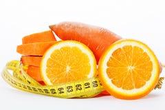 Scheiben der Orange mit Scheiben der Karotte und des messenden Bands Lizenzfreies Stockbild
