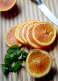 Scheiben der Orange mit tadellosen Blättern auf hölzernem Schreibtisch Stockfotografie